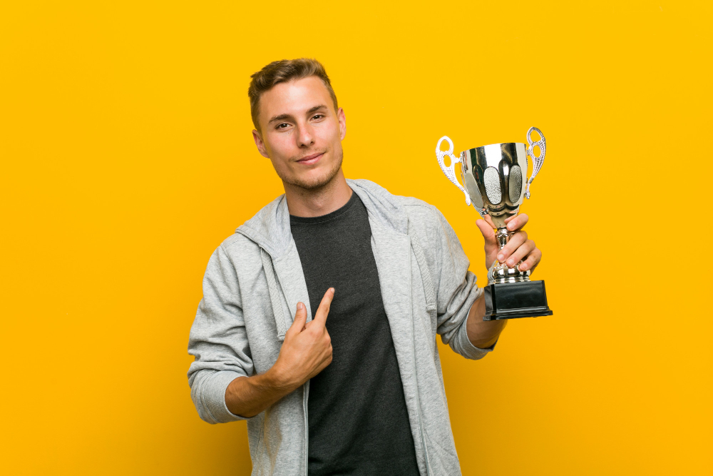 young caucasion man holding trophy